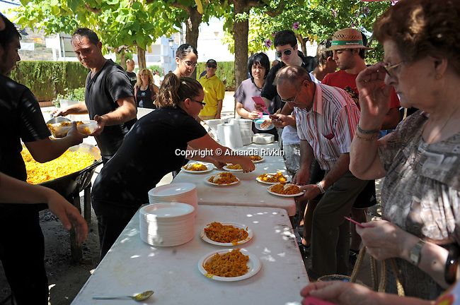 Villagers wait in line with tickets for a serving of fideua, a traditional Valencian seafood macaroni dish not unlike paella, for 400 before a lunch for the entire town during the  municipal fiestas in Costur, Spain on August 19, 2009.