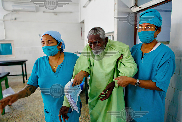 A patient is helped by surgeons after having an operation at the GETA eye hospital.