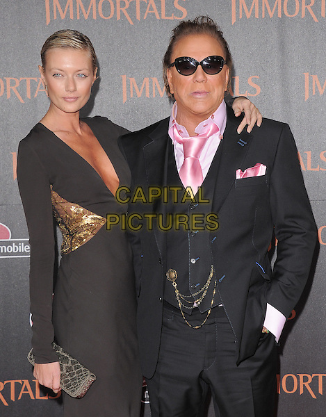 Irson Kudikova & Mickey Rourke.The World Premiere of 'Immortals' held at The Nokia Theater Live in Los Angeles, California, USA..November 7th, 2011.half length brown low cut neckline cleavage gold sequins sequined clutch bag black suit waistcoat pink shirt sunglasses shades couple arm over shoulder.CAP/RKE/DVS.©DVS/RockinExposures/Capital Pictures.