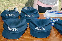 """Hats and shirts reading """"MATH"""" are seen on a table with campaign materials as entrepreneur and Democratic presidential candidate Andrew Yang speaks at a campaign rally in Cambridge Common near Harvard Square in Cambridge, Massachusetts, on Mon., September 16, 2019. Yang's unlikely presidential bid is centered on his idea for a """"Freedom dividend,"""" which would give USD$1000 per month to every adult in the United States. After appearing in three Democratic party debates, Yang has risen in polls from longshot candidate to within the top 10. The slogan MATH is now said to mean """"Make America Think Harder"""" and the candidate frequently sites statistics and mathematics in his speeches."""