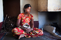 Nitu (not her real name), looks outside from her kitchen in Jhaju village, Bikaner, Rajasthan, India on 4th October 2012. Now 18, she was married off at age 10 to a boy of around the same age, but only went to live with her in-laws when she was 12, after she had finished studying up to class 6. The three sisters, aged 10, 12, and 15 were married off on the same day by their maternal grandfather while their father was hospitalized. She was abused by her young husband and in-laws so her father took her back after hearing that her husband, who works in a brick kiln, was an alcoholic and was doing drugs and crime. She had only spent a few days at her husband's house at that time. Her father (now out of the hospital) has said that she will only be allowed to return to her husband's house if he changes his ways but so far, the negotiations are still underway. Photo by Suzanne Lee for PLAN UK
