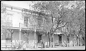 Close-in view of front fa?ade of St. James Hotel with trees, covered veranda and one woman standing by entrance.<br /> Cimarron, NM  Taken by Goodwin, H. Sage - ca 1929