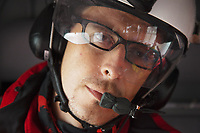 "Switzerland. Canton Ticino. Osogna Bresciano. The Doctor Michele Musiari is seated inside the cabin of a flying Rega Agusta AW109 SP Grand ""Da Vinci"" helicopter. All Rega helicopters carry a crew of three: a pilot, an emergency physician, and a paramedic who is also trained to assist the pilot for radio communication, navigation, terrain/object avoidance, and winch operations. The name Rega was created by combining letters from the name ""Swiss Air Rescue Guard"" as it was written in German (Schweizerische Rettungsflugwacht), French (Garde Aérienne Suisse de Sauvetage), and Italian (Guardia Aerea Svizzera di Soccorso). Rega is a private, non-profit air rescue service that provides emergency medical assistance in Switzerland. Rega mainly assists with mountain rescues, though it will also operate in other terrains when needed, most notably during life-threatening emergencies. As a non-profit foundation, Rega does not receive financial assistance from any government. The AgustaWestland AW109 is a lightweight, twin-engine, helicopter built by the Italian manufacturer Leonardo S.p.A. (formerly AgustaWestland, Leonardo-Finmeccanica and Finmeccanica). Leonardo S.p.A is an Italian global high-tech company and one of the key players in aerospace. In close collaboration with the manufacturer, the Da Vinci has been specially designed to cater for Rega's particular requirements as regards carrying out operations in the mountains. It optimally fulfills the high demands made of it in terms of flying characteristics, emergency medical equipment and maintenance. Safety, performance and space have been increased, and maintenance and noise emissions reduced. 9.09.2017 © 2017 Didier Ruef"