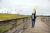 USA, Washington State, Long Beach Peninsula, International Kite Festival, a French woman flies a kite along the popular Long Beach Boardwalk