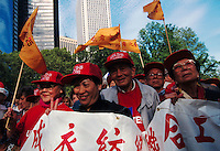 (970522-SWR05)--File Photo -- New York, NY -- A group of Asian immigrants wearing red Unite t-shirts and red Local 23-45 baseball caps carry a banner with chinese characters and wave yellow flags. Thousands of immigrants gathered in Battery Park, in the shadow of the Statue of Liberty and Ellis Island, for a Rally for Immigrants Rights.  Photo © Stacy Walsh Rosenstock