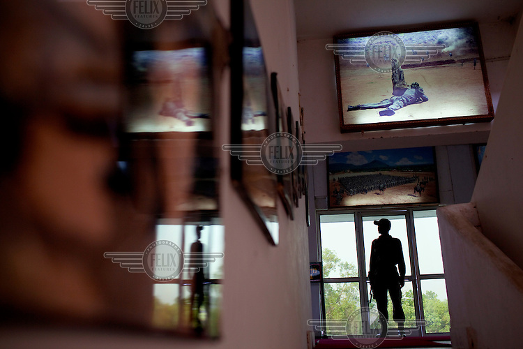 A police sentry standing guard outside of Brigadier B.K. Ponwar's office is reflected in photographs of training exercises hanging in the Counter-Terrorism & Jungle Warfare College in Kanker. /Felix Features