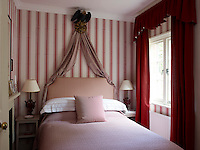 This guest bedroom is a pretty confection of red and pink with a corona above the double bed in the shape of an Imperial eagle