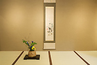 Traditional Japanese details of a hanging scroll and flower arrangements over the tatami matting.