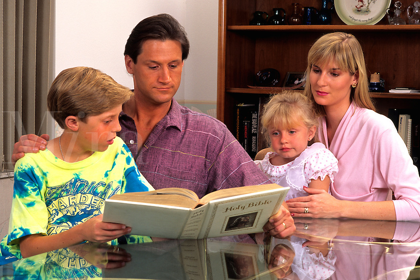 American family spending time together around the table reading the bible at home