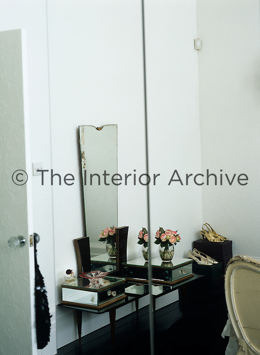 An Art Deco dressing table in the bedroom is reflected in the mirrored doors of the built-in cupboard