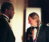 """Singer and songwriter Willie Nelson arrives in the East Room of the White House in Washington, D.C. on December 6, 1998 as part of the """"1998 Kennedy Center Honors"""" festivities.  Actor, comedian Bill Cosby looks on..Credit: Ron Sachs - CNP"""