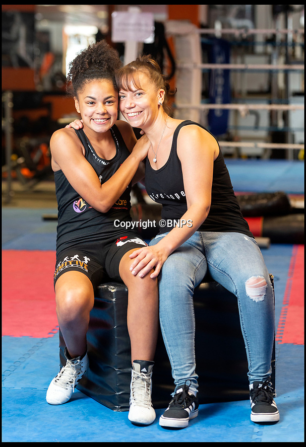 BNPS.co.uk (01202 558833)Pic: RogerArbon/BNPS<br /> <br /> Gabrielle Reid with her mum Lisa at Primitive Gym in Poole, Dorest.<br /> <br /> An inspiring 14 year old girl with cerebral palsy who was once wheelchair bound has taken part in her boxing match - and she won.Gabrielle Reid was born with right hemiplegia which affects her muscle control and movement making it difficult to walk, let alone spar in the ring.However, since taking up boxing five years ago, her movement and coordination have improved to such an extent that she has just competed in her first bout in her home town of Poole, Dorset.She defeated a fully able bodied fighter in a three round contest and has now set her sights on her second bout, scheduled for October.