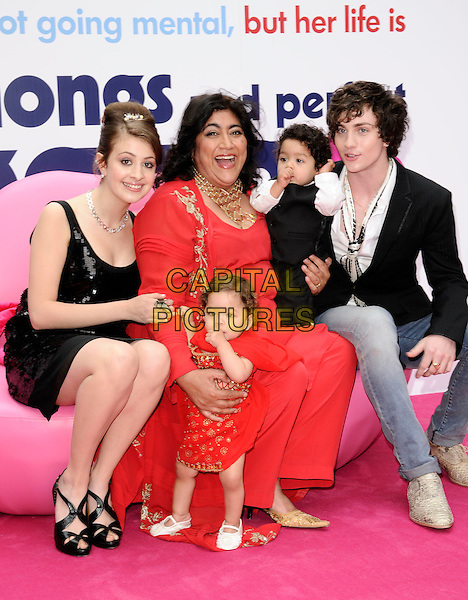 "GEORGINA GROOME, GURINDER CHADHA, AARON JOHNSON & children.The UK Film Premiere of ""Angus, Thongs and Perfect Snogging"", Empire cinema, Leicester Square, London, England..July 16th 2008.full length red dress kids gold necklace director sitting pink lips sofa seat black dress jeans denim jacket sequins sequined.CAP/CAN.©Can Nguyen/Capital Pictures."