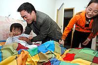Li Daquan (centre) et Qiang Yun (droite) couchent Li Siqi (gauche) dans le grand lit où ils dorment tous les trois. Li Siqi refuse de dormir dans son lit de bébé et a envahi celui de ses parents, sans que personne ne proteste. A Baoshan, près de Shanghai, le 10 mai 2008. Photo par Lucas Schifres/Pictobank