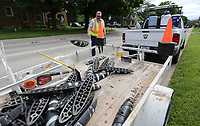 Eric Carter (left) and Chris Myers, both with signs and markings with the city of Springdale Public Works, remove Zebra bike lane delineators Tuesday, May 19, 2020, on Maple Avenue in Springdale. The Zebras will remain in the area near Northwest Medical Center and LISA Academy but be removed from other streets. The removed Zebras will be replaced with a raised pavement marker. Check out nwaonline.com/200519Daily/ and nwadg.com/photos for a photo gallery.<br /> (NWA Democrat-Gazette/David Gottschalk)