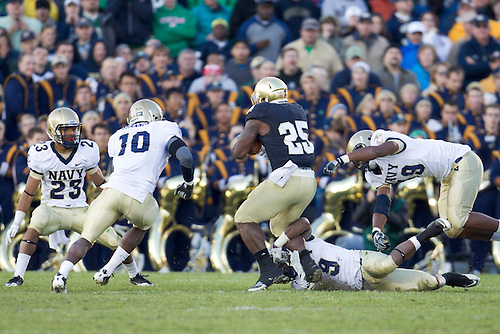 Notre Dame tailback Jonas Gray (#25) is pursued by Navy defensive players during third quarter of NCAA football game between Notre Dame and Navy.  The Notre Dame Fighting Irish defeated the Navy Midshipmen 56-14 in game at Notre Dame Stadium in South Bend, Indiana.