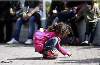 Pictured: A girl plays amongst adult migrants at the port Tuesday 01 March 2016<br /> Re: Migrants at the port of Piraeus, near Athens, Greece