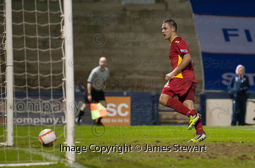 Pars' Stephen Husband rolls the ball into an empty net to score Dunfermline's third  ...
