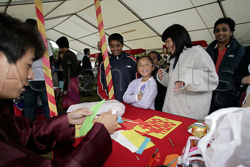 24 July 2005: Demonstration of Chinese paper-cutting at Newbury on Hong Kong Day Photo: Glyn Kirk/actionplus...horse ascot 050724 child girl children