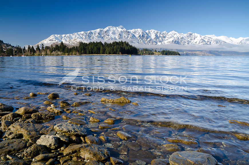 Looking across Lake Wakatipu to the snow covered Remarkable Mountains and Queenstown Gardens, South Island, New Zealand
