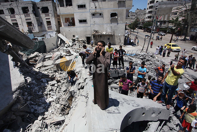 "A Palestinian muezzin ""caller of Muslims to Mosque for daily prayers"", preforms for noon prayer as he stands on the debris of  al-Shuhada mosque, which witnesses said was hit by an Israeli air strike, in Nuseirat refugee camp in the central Gaza Strip on August 10, 2014. Israel said on Sunday it was prepared for protracted military action in Gaza and would not return to Egyptian-mediated ceasefire talks as long as Palestinians kept up cross-border rocket and mortar fire. Israeli air strikes and shelling killed three Palestinians in Gaza on Sunday, including a boy of 14 and a woman, medics said, in a third day of renewed fighting that has jeopardised international efforts to end a more-than-month-old conflict. Photo by Ashraf Amra"