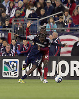 New England Revolution midfielder Shalrie Joseph (21) attempts to control the ball as Real Salt Lake midfielder Jean Alexandre (12) defends. In a Major League Soccer (MLS) match, Real Salt Lake defeated the New England Revolution, 2-0, at Gillette Stadium on April 9, 2011.