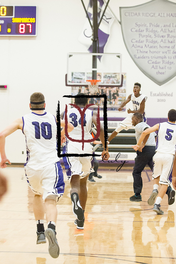 The Cedar Ridge basketball team celebrates an overtime win against San Marcos November 21, 2014 at Cedar Ridge Gym.