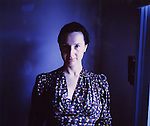 A middle aged woman wearing a blue dress looking at the camera