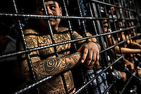 "A member of the 18th Street gang (M-18) stands behind the bars in a cell at the detention center in San Salvador, El Salvador, 20 February 2014. Although the country's two major gangs reached a truce in 2012, the police holding cells currently house more than 3000 inmates, five times more than the official built capacity. Partly because the ordinary Mara gang members did not break with their criminal activities (extortion, street-level distribution of drugs, etc.), partly because Salvadorean police still applies controversial anti-gang law which allows to detain almost anyone for ""suspicion of gang membership"". Accused young men are held in police detention centers where up to 25 inmates may share a cell of five-by-five metres. Here, in the dark overcrowded cages, under harsh and life-threatening conditions, suspected gang members wait long months, sometimes years, for trial or for to be transported to a regular prison."