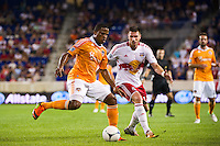 Jermaine Taylor (4) of the Houston Dynamo is marked by Kenny Cooper (33) of the New York Red Bulls. The New York Red Bulls defeated the Houston Dynamo 2-0 during a Major League Soccer (MLS) match at Red Bull Arena in Harrison, NJ, on August 10, 2012.