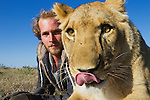 Botswana, Kalahari, Valentin Gruener cuddling with a lioness; he raised her on a private reserve from a small dying cub to a healthy adult