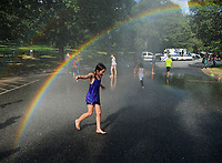 NWA Democrat-Gazette/ANDY SHUPE<br /> Ryla Harris, 8, of Fayetteville plays Tuesday, Aug. 6, 2019, in water sprayed by a Fayetteville Fire Department engine during the National Night Out event at Wilson Park. Night Out events are organized to foster stronger relationships between local law enforcement and community members and to build bonds among neighbors through similar events across the country on the first Tuesday of August. Central EMS, Fayetteville Fire and Police departments, Arkansas Highway Patrol and State Police joined city departments and other vendors in the annual event.