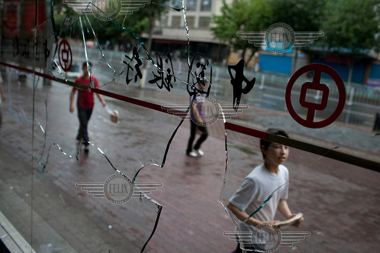 Uighurs pass a Bank of China window that was smashed during riots in the Uighur district of Urumqi. Ethnic violence between the Uighur and Han Chinese people had erupted in the city a few days earlier.