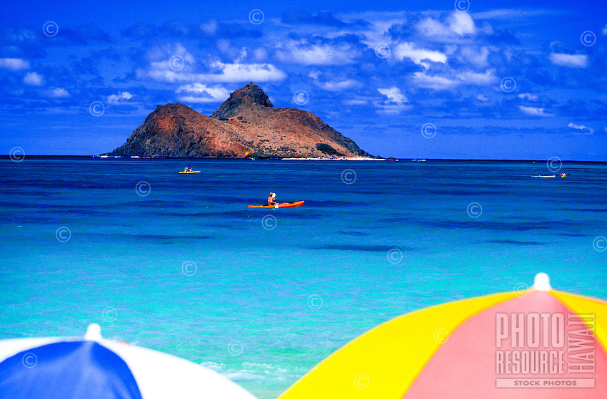 Framed by colorful beach unbrellas,a kayaker paddles thru the clear blue waters off Lanikai Beach with the scenic Moku lua islands in the background.  Windward Oahu.