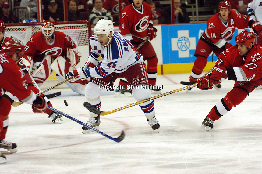 Carolina Hurricanes' Craig Adams (27) pokes at a puck in front of the New York Rangers' Martin Rucinsky (26) of the Czech Republic during their game Tuesday, March 14, 2006 at the RBC Center in Raleigh, NC. Carolina won 5-3.