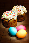 Painted with light Easter cakes and colorful Easter eggs Artistic festive still life on dark background Vertical orientation