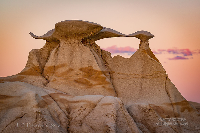 Winged Portal Arch, Bisti Badlands, New Mexico ©2016 James D Peterson.  This elegant little window was basking in the sunset's afterglow while the clouds in the background were warmed by the last rays of sunlight.