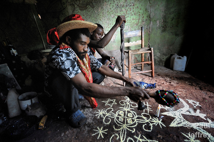 Acasekam Saint Jerar (left), a voodoo priest, performs a ceremony in Mizak, a small village in the south of Haiti. He is assisted by Pouchon Frederique.