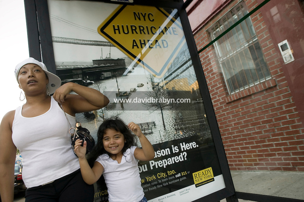 10 September 2005 - New York City, NY - Ramonita Rosa (L) and daughter, 4 year-old Ariana, wait for their bus under a shelter carrrying a poster alerting New-Yorkers to hurricane preparedness in the Greenpoint neighborhood of Brooklyn, New York, USA, 10 September 2005. The campaign, which was planned by the Office of Emergency Management long before Katrina hit southern states, went up across town during the first days of September. The zones at highest risk include lower Manhattan, Brooklyn's Coney Island, the Rockaways in Queens and the perimeter of Staten Island. Hurricane season in New York is from August to October, when waters along the East Coast are warmer. The city's worst hit, in 1938, caused more than 600 deaths. Photo Credit: David Brabyn.