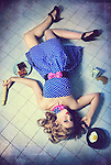 A young blonde woman sprawled out on a kitchen floor in a polkadot dress with spilled coffee and burnt toast