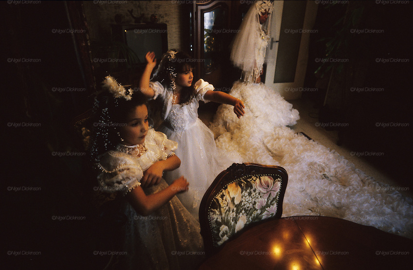Kaly's bridesmaids dance to rhumba music, on the morning of her wedding. The train of her dress all but fills the living room of her family's apartment. Montpellier, France 1994