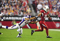 Dec 6, 2009; Glendale, AZ, USA; Arizona Cardinals wide receiver (11) Larry Fitzgerald runs past a diving Minnesota Vikings safety (25) Tyrell Johnson in the second quarter at University of Phoenix Stadium. Mandatory Credit: Mark J. Rebilas-