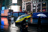 NEW YORK, NY - April 13:  People wearing face masks walk around Times Square during a rainy day on April 13, 2020. in New York, United States. The global economy is facing the worst collapse since the WWII, while COVID-19  pandemic has now killed more than 22,000 people in the United States and at least 1,864,629 people died world wide. (Photo by Eduardo MunozAlvarez/VIEWpress)