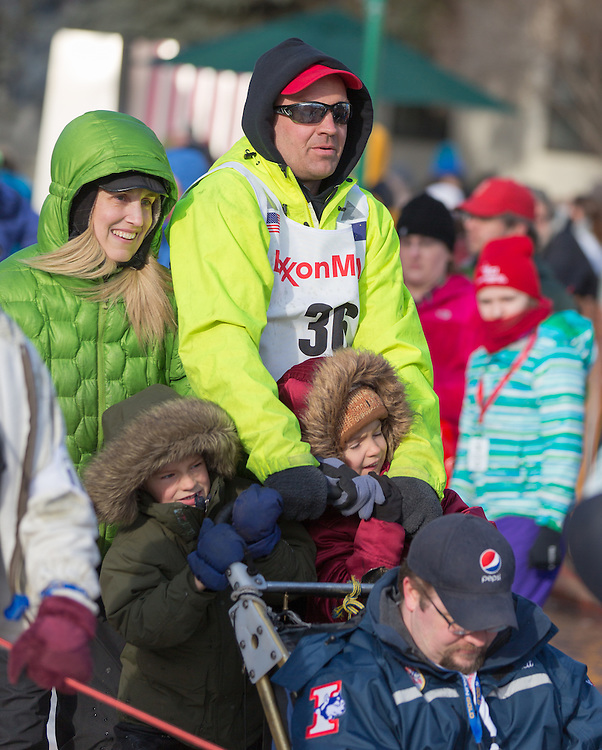 Musher Ken Anderson, from Fairbanks, is accompanied by his family as he steers his dog team to the ceremenial start of the 43rd Annual Iditarod in Anchorage, Alaska. The 1000 mile dog sled race usually restarts in Willow, Alaska, and finishes in Nome. Poor snowfall, however, forced the restart north to Fairbanks.