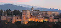 The Alhambra Palace illuminated at night, Granada, Andalusia, Southern Spain, with the Comares Tower, built in the 14th century under Muhammad V, the tallest tower in the Alhambra and housing the Hall of the Ambassadors, Nasrid Palaces and the Palace of Charles V in the background, built by Pedro Machuca in the 16th century. The Alhambra was begun in the 11th century as a castle, and in the 13th and 14th centuries served as the royal palace of the Nasrid sultans. The huge complex contains the Alcazaba, Nasrid palaces, gardens and Generalife. Behind are the snow-capped peaks of the Sierra Nevada. Picture by Manuel Cohen