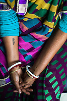 Brinda, one of the 57 underaged and trafficked girls rescued from the Shivdaspur red light area in Varanasi, looks at her torture scars and a tattoo of her 'brothel-given nickname' on her hands as she sits in the legal room in the Guria office in Varanasi, Uttar Pradesh, India on 22 November 2013. She has been fighting a court case against her traffickers and brothel owners for the past 8 years with the help of NGO Guria Swayam Sevi Sansthan