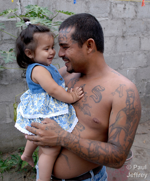 Henri Aguilar with his one-year old daughter Genesis in the yard of their home in Honduras. This photo was captured May 2, 2007. On May 7, 2007, he was assassinated by three masked men. Aguilar was a former member of the Mara Salvatrucha, but under the guidance of a Catholic program had left the gang and was married, working full time, and heavily involved in parish life. No one has been charged with his murder.