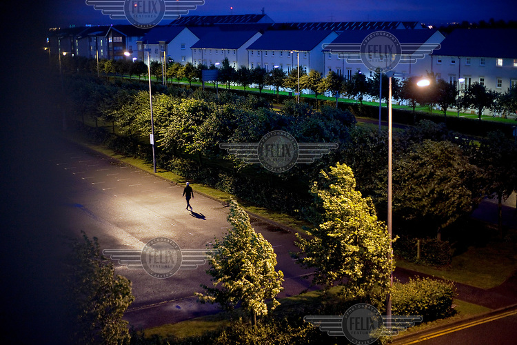 A man walks through a pool of lamp light in an empty car park.