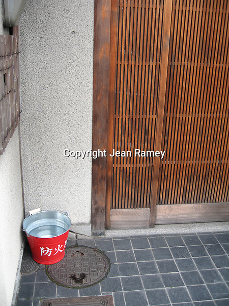 A fire brigade bucket of water sits outside the historic wooden houses in Kyoto
