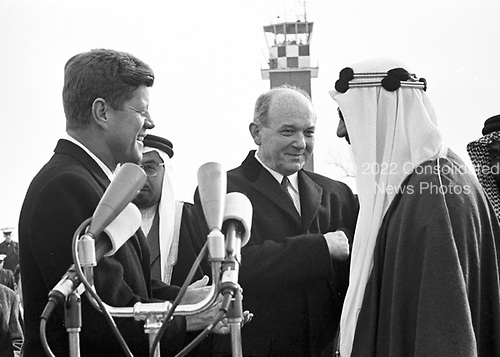 United States President John F. Kennedy welcomes King Saud of Saudi Arabia at Andrews Air Force Base outside Washington, DC on February 13, 1962.  United States Secretary of State Dean Rusk looks on at center..Credit: Arnie Sachs / CNP